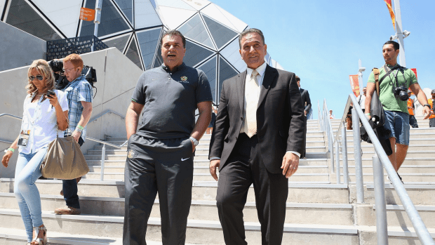 Australian Socceroos Coach Ange Postecoglou and Victorian Minister for Tourism and Major Events, John Eren are seen as they leave the stadium.