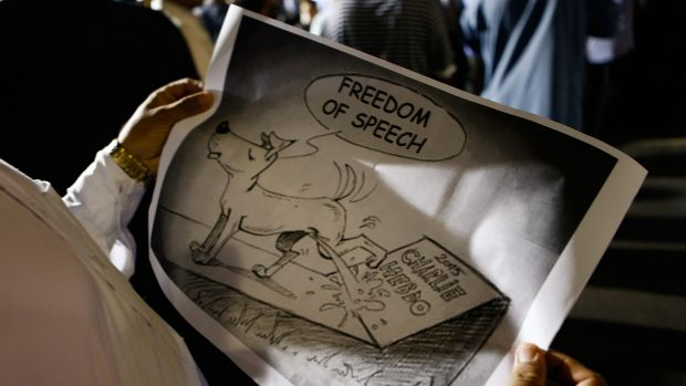 A Muslim holds a cartoon during a rally to show their support for the Prophet Muhammad in Lakemba on Friday.