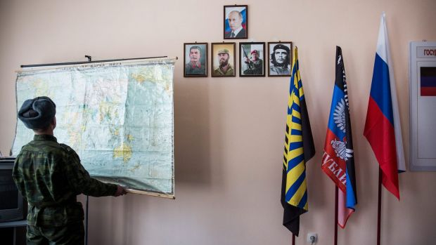 "A pro-Russian rebel adjusts a map near  portraits of Vladimir Putin, Stalin, Fidel Castro, Hugo Chavez and Che Guevara at ""Battalion Kalmius"" headquarters in rebel-held Donetsk, Ukraine."