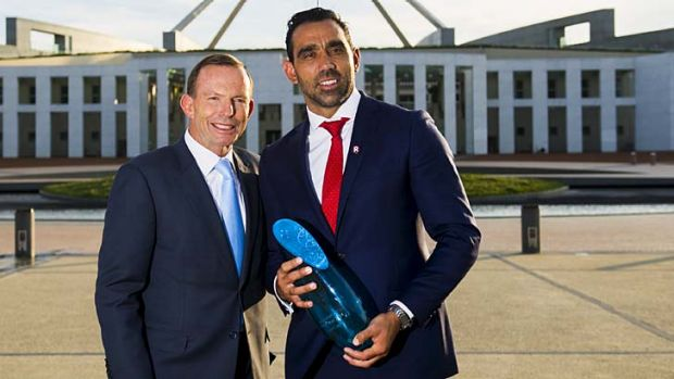 Adam Goodes holding Australian of the Year statue standing next to Tony Abbott.