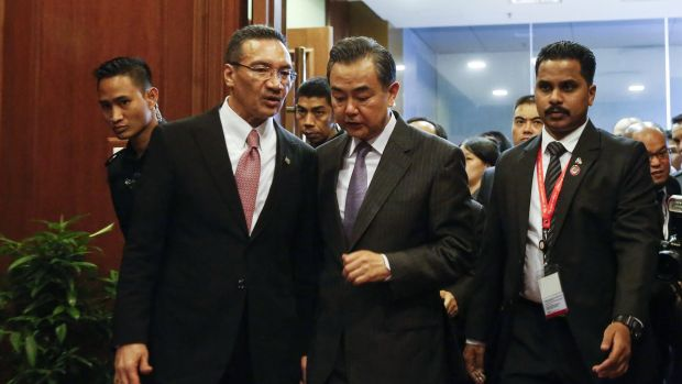 Chinese Foreign Minister Wang Yi, centre, speaks to Malaysian Defence Minister Hishammuddin Hussein in Kuala Lumpur on Tuesday.