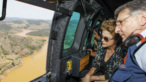 Brazilian President Dilma Rousseff, accompanied by Minas Gerais state governor Fernando Pimentel, looks out over the dam ...