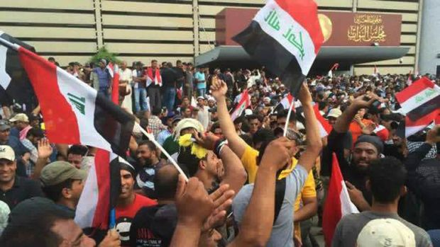 Protesters raise the Iraqi flag outside parliament in Baghdad's Green Zone.