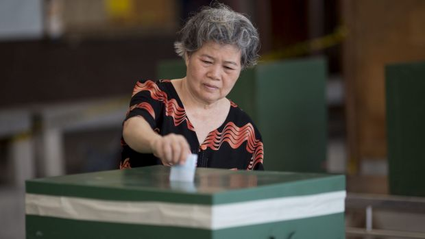 A voter casts a ballot at a polling station on August 7 in Bangkok, Thailand.