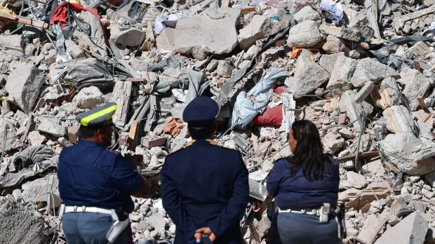 Police officers view the remains of a building in Amatrice following the deadly quake.