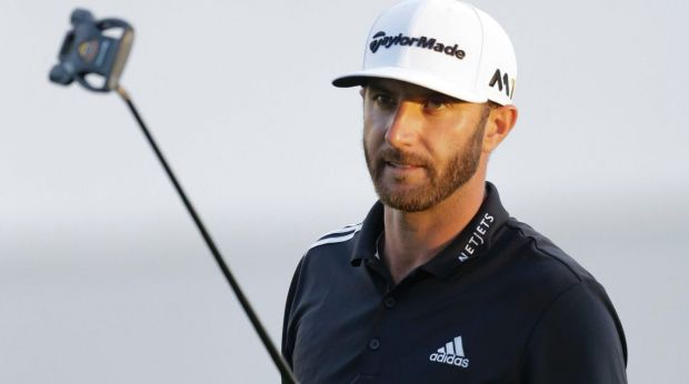 Dustin Johnson acknowledges the crowd after finishing the round on the 18th hole.