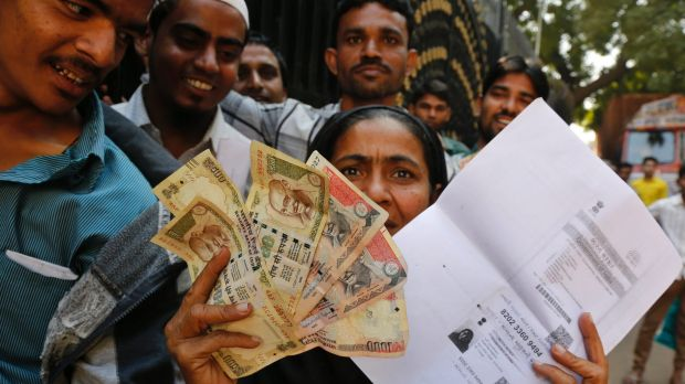An Indian woman shows discontinued Indian currency notes and a photocopied ID card as she queues outside Reserve Bank of ...