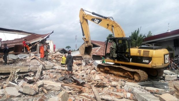 Heavy equipment cleans up a petrol station coffee shop where 10 people were thought to be trapped.