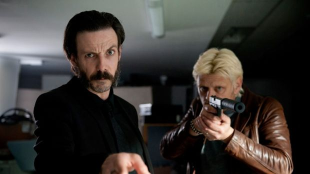 Your attention please: Workplace expert Menkoff (Noah Taylor) with colleague.