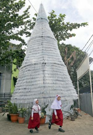 Two school girls walk past a Christmas tree made from 6000 discarded water bottles outside of a church in Depok, ...