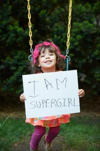 super girl needs braces orthodontist holding sign.