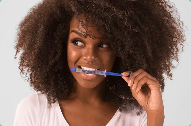 clareamento dental caseiro. mulher com a seringa do clareador dental na boca