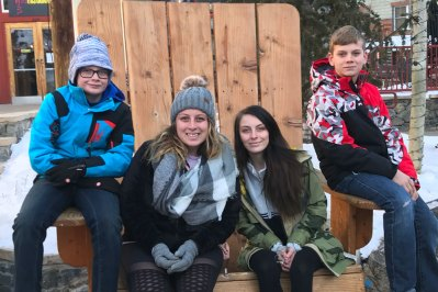 Family posing in giant chair during winter
