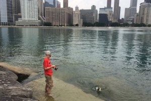 Boy in red shirt standing in water fishing with city skyline behind him.