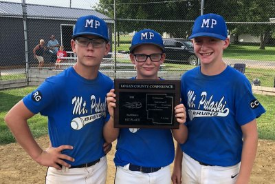 Three boys in blue Mt. Pulaski Bruins uniforms holding 1st Place Conference plaque
