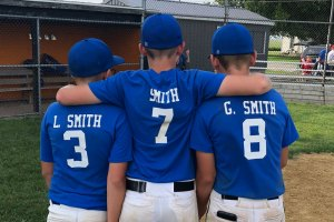 Smith boys in blue baseball uniforms showing their names and numbers on the back