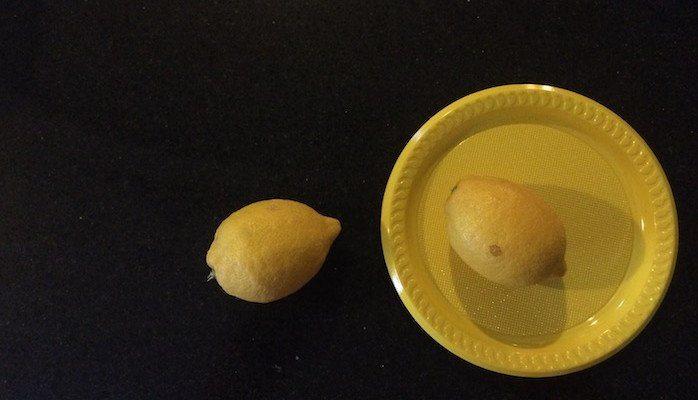2 lemons and a yellow plate
