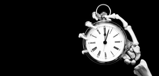 Skeleton hand holds deadline stopwatch