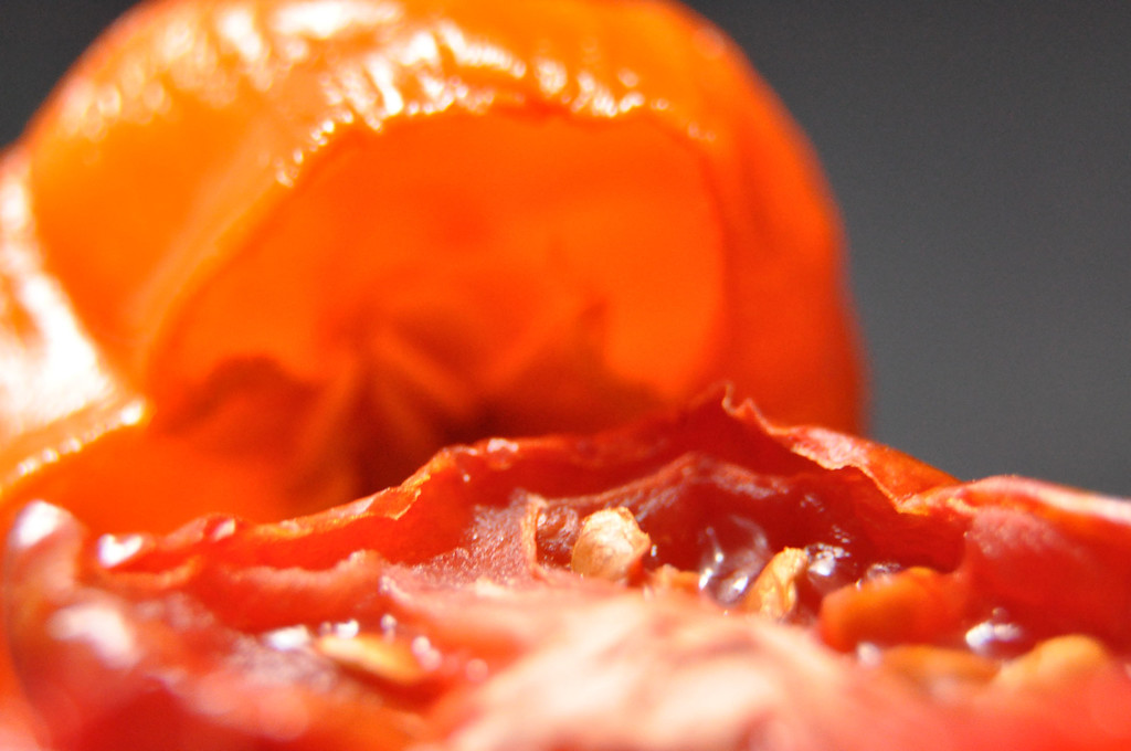 A close up of a wilted, sliced tomato with an orange sweet pepper in the background.