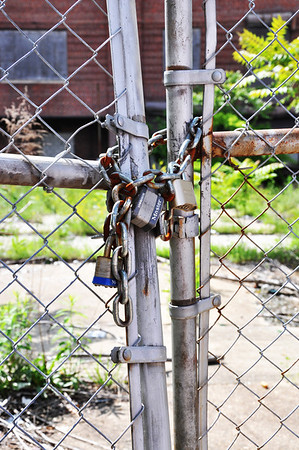 A gate in a wire fence closed with a loose chain and a padlock.