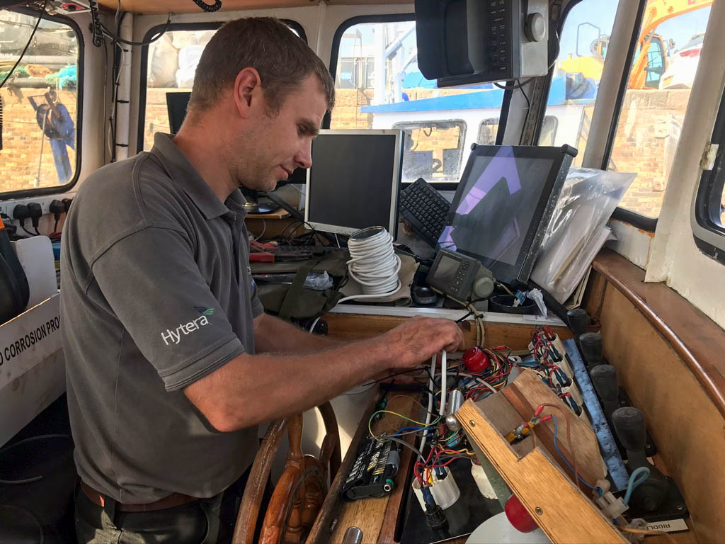 Luke working on a trawlers marine electronics system at whitstable