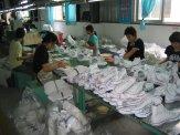Los operarios empaquetan las zapatillas.