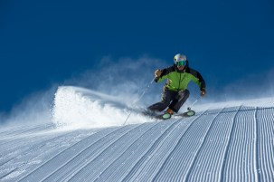 Chris Davenport skiing down fresh corduroy on a steep snow covered groomed slope in the mountains at Aspen Mountain Ski Resort in Colorado