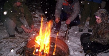people sitting around a campfire in winter