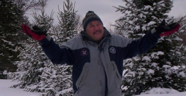 """man on snowshoes with arms raised in a """"why not"""" position"""