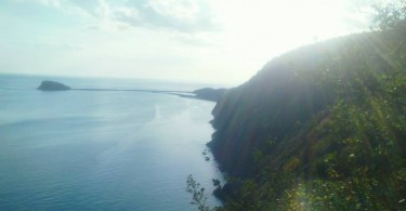 sun shining off the sea cliffs with water in background
