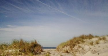 view of sand dunes under open blue sky and wisps of clouds