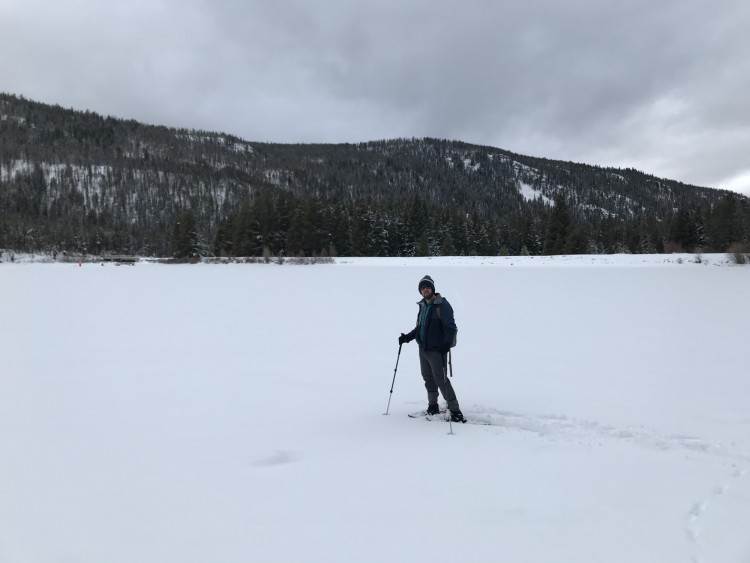 man standing on snowy frozen lake in snowshoes