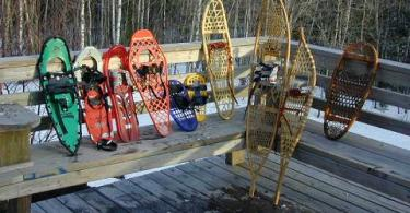 several types of snowshoes lined up on outdoor deck