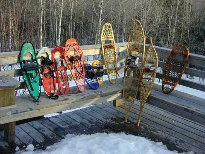 snowshoe storage: modern and traditional snowshoes on snow covered deck