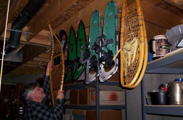 snowshoe storage: man hanging up snowshoes in garage for storage