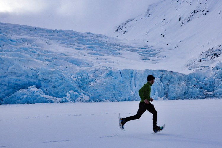 man running on snowshoes in snowy landscape