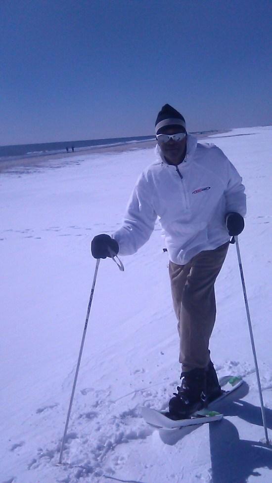 man on Crossblades with poles on snow near Atlantic Ocean