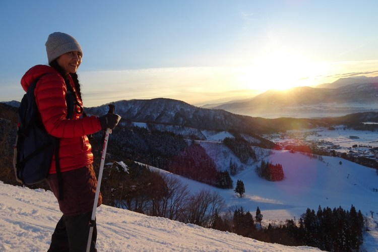 woman on snowshoes on mountain with sunset
