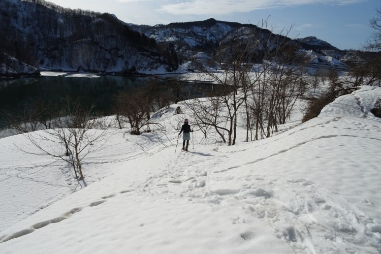 snowshoeing near Sanjo, Niigata: person in distance on snowshoe trail with snowshoe tracks in foreground and mountains in background