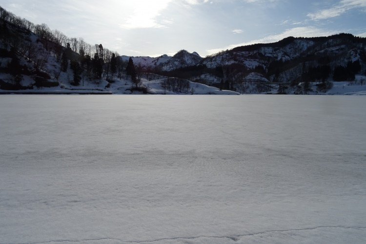 snow covered lake with mountains and open sky in background
