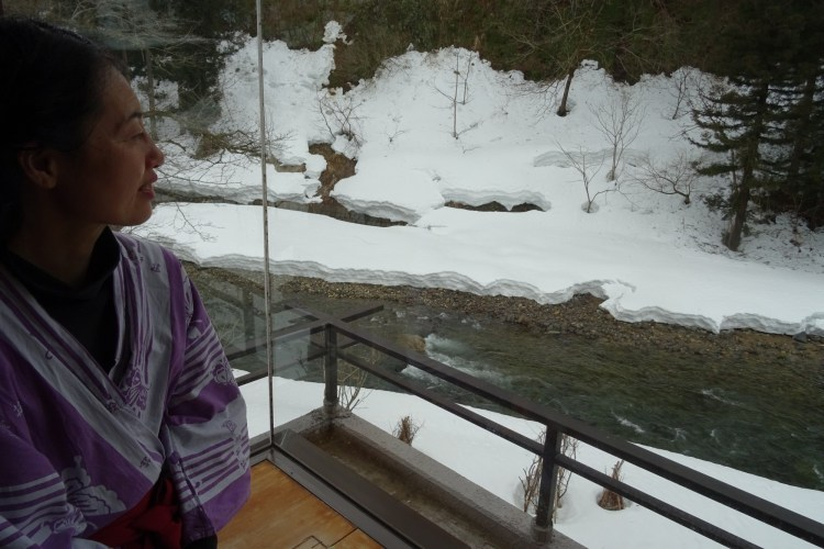 woman looking out from balcony at river and snow
