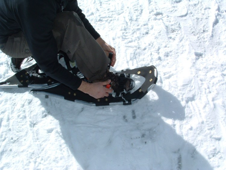 snowshoeing tips: person putting on their snowshoe