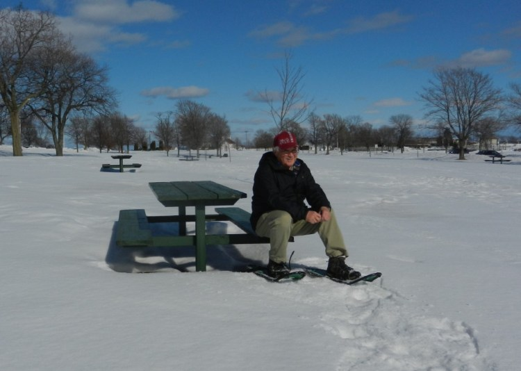 taking a break on a bench from snowshoeing
