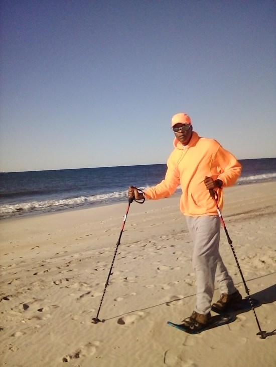 snowshoes on sand for fitness: man on beach wearing snowshoes and using poles