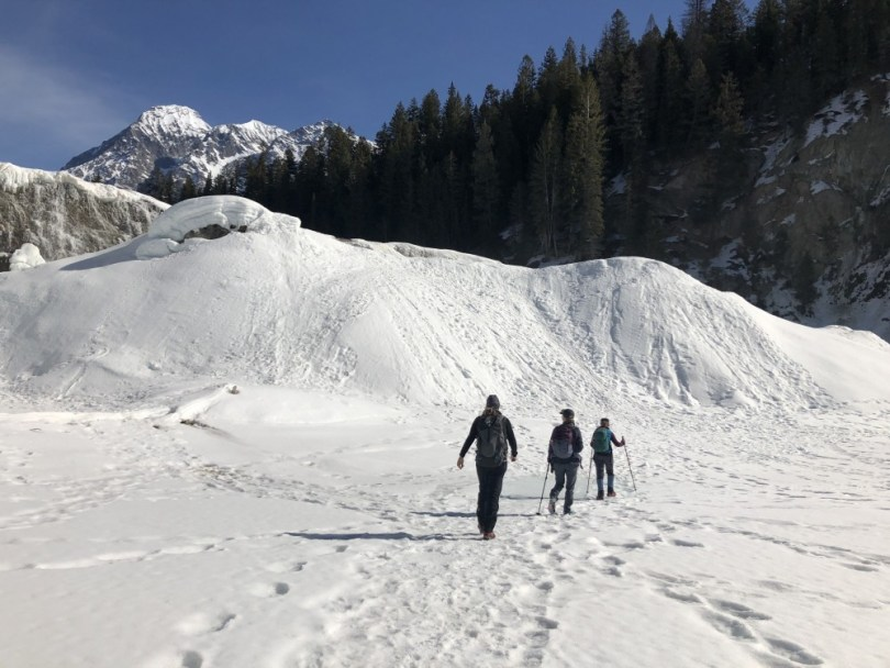 three people snowshoeing in distance to Wapta Falls, Canada
