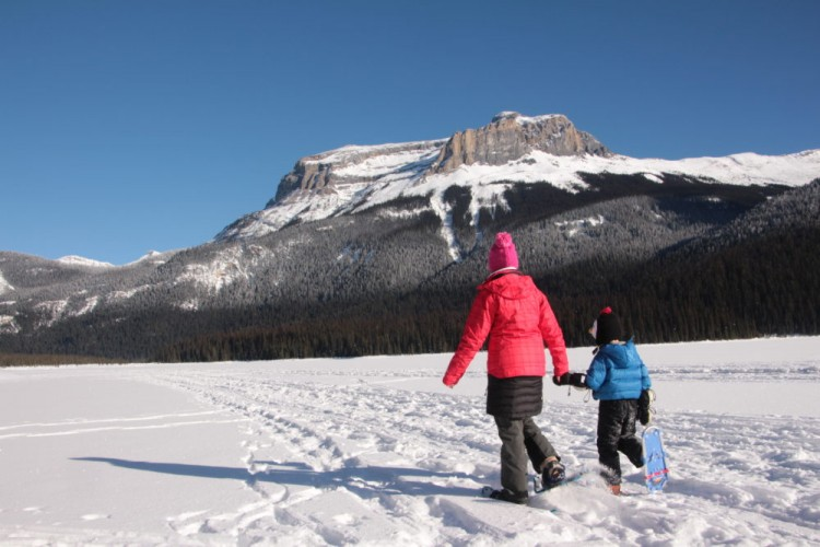 adult and child snowshoe across Emerald Lake hand in hand
