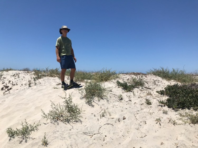 man on snowshoes standing on dune near beach