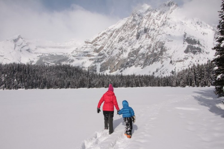 adult and child snowshoeing in deep powder