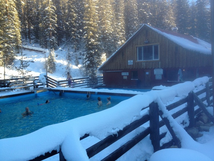 hot springs pool with people and snowy fence in the foreground