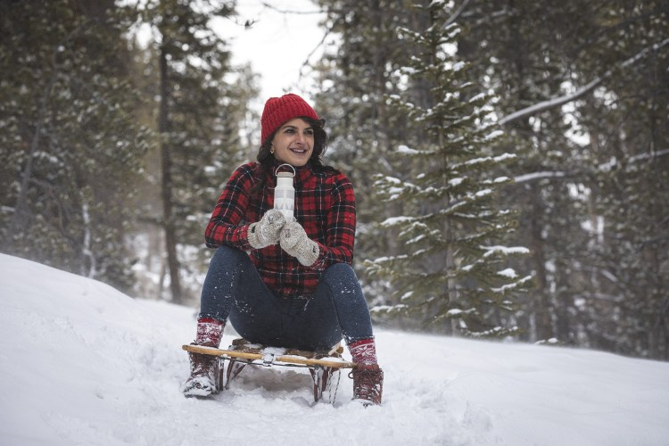 Woman on a sleigh in the snow holding a 12 oz Klean Kanteen vacuum flask